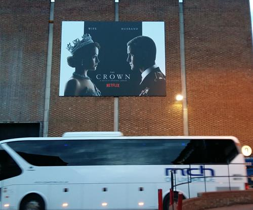 'The Crown' outdoor flex-face sign high above Elstree Studios service road.