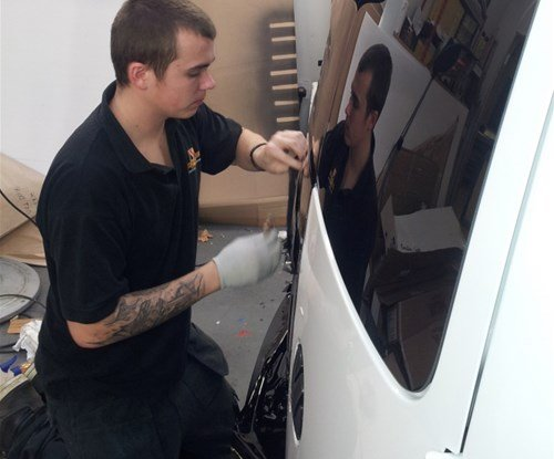 Brandon Desborough applying vehicle graphics