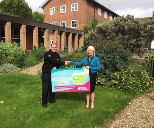 Danny Booth presents Jacqui Peel with her prize of a golf lesson for two