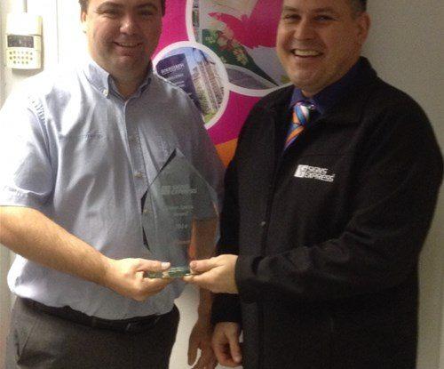 Tony Surface of Signs Express Basildon accepting his award from managing director Craig Brown