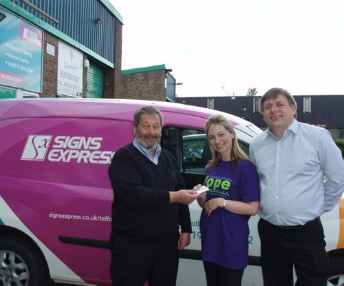 Carrie Fulcher and Kris Allen collecting the tickets from Gary at Signs Express (Telford)