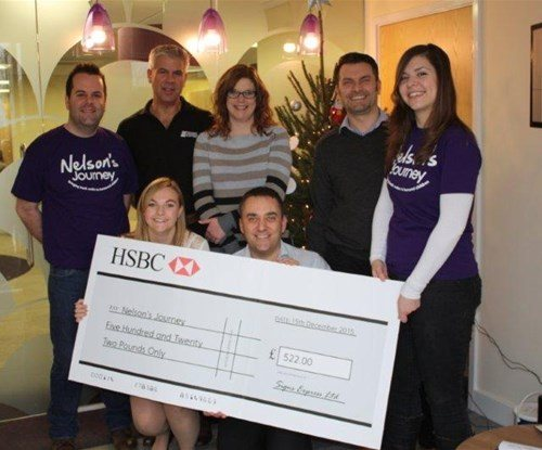 The Signs Express team handing the cheque over to Nelson's Journey