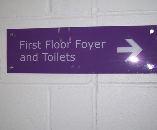 Internal directional sign in acrylic mounted on brushed stainless stand offs