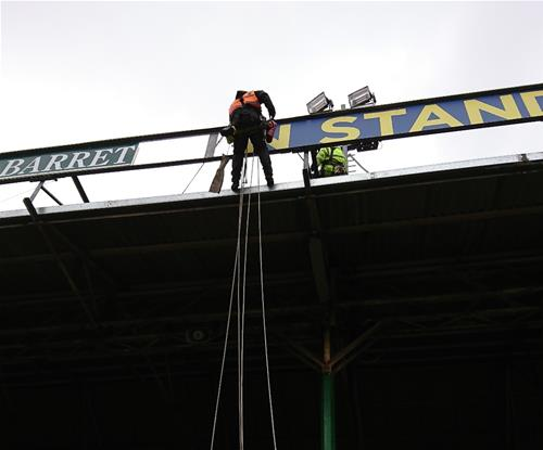 The rope access crew removing the Holland & Barrett branding & replacing with the Breedon branding