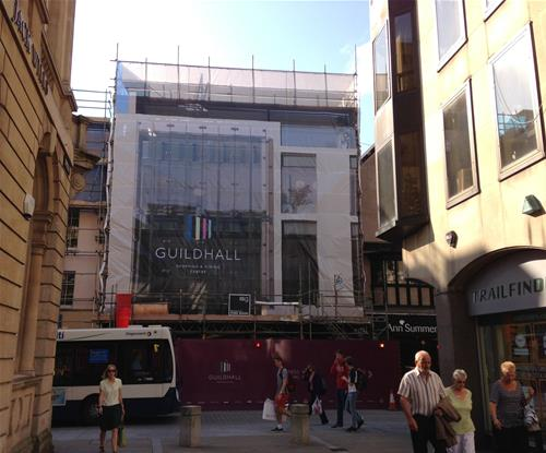 Large mesh banner on scaffolding advertising entrance to Guildhall shopping centre during project works.