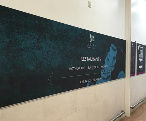 Large tensioned wall graphic as part of wayfinding scheme