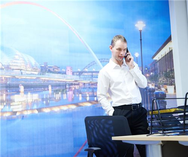 Adam Greaves at his new Cramlington production unit with a large wall graphic of Newcastle shown