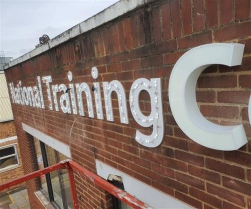 High level installation of external signs in progress.