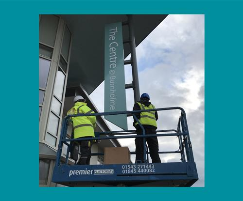 External projecting sign being installed at height