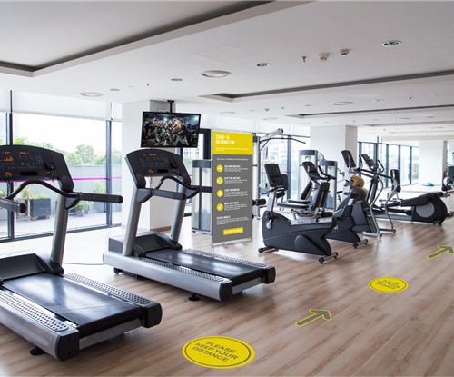 Social distancing gym with Coronavirus signage and floor markings